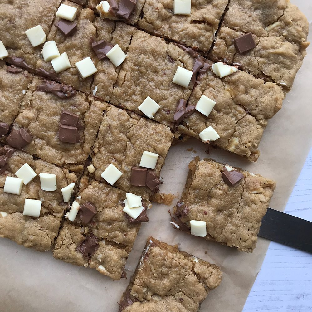 Peanut butter cookie cake, with chocolate drops in a slab on greaseproof