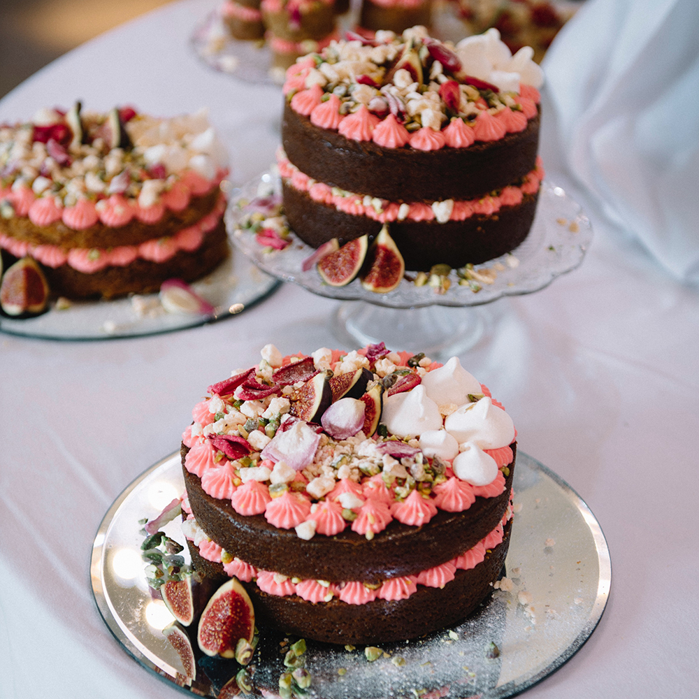 Persian love cakes as part of a wedding dessert table. Decorated with meringues, figs, pistachios and rose petals, this caramel cake with rose buttercream is a visual delight.