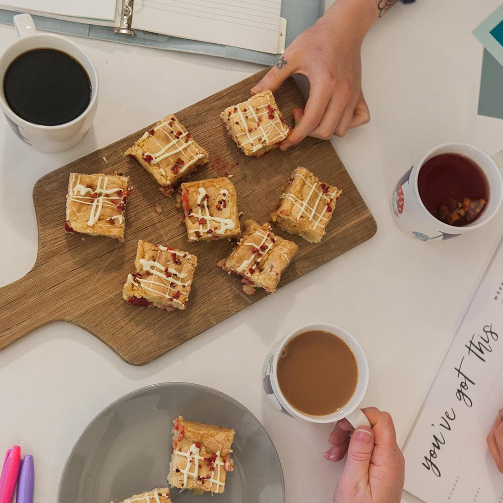 Raspberry and white chocolate brownie being shared with colleagues during a planning meeting