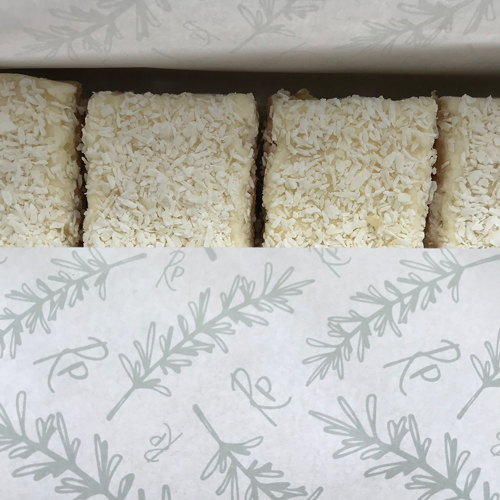 Coconut cake wrapped in Rosemarie's Pantry branded greaseproof