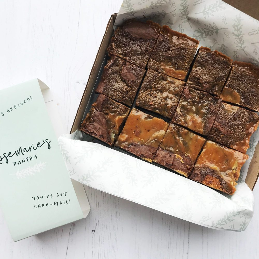 Open box with salted caramel brownie, showing the branded kisses paper and belly band.